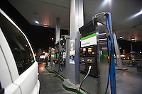Close up of cat at gas station fuel pumps with natural gas at night
