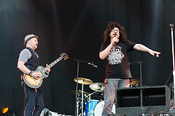© Licensed to London News Pictures. 12/06/2015. Newport, UK.   Counting Crows performing live at Isle of Wight Festival 2015, Day 2 Friday.  In this picture - Dan Vickrey (left), Adam Duritz (right).  This afternoon has seen torrential downpours of rain after the last day of hot sunshine.   Photo credit : Richard Isaac/LNP
