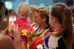 © Licensed to London News Pictures. 23/08/2016. London, UK. Women's hockey champion Lily Owsley shows her gold medal to her two-year-old daughter Charlotte as Team GB arrives at terminal 5 of London Heathrow Airport on British Airways flight BA2016, decorated with a gold nose. Team GB finished second in the medals table with 67 medals, beating their total of 65 at London 202.  Photo credit: Ben Cawthra/LNP