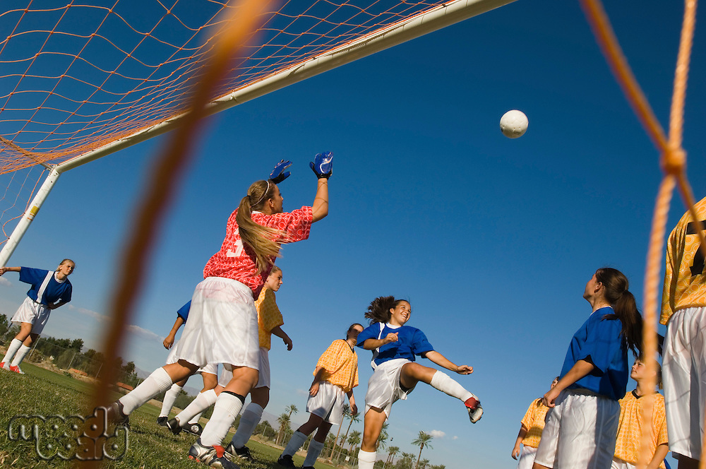 Girl (13-17) waiting to score with soccer ball