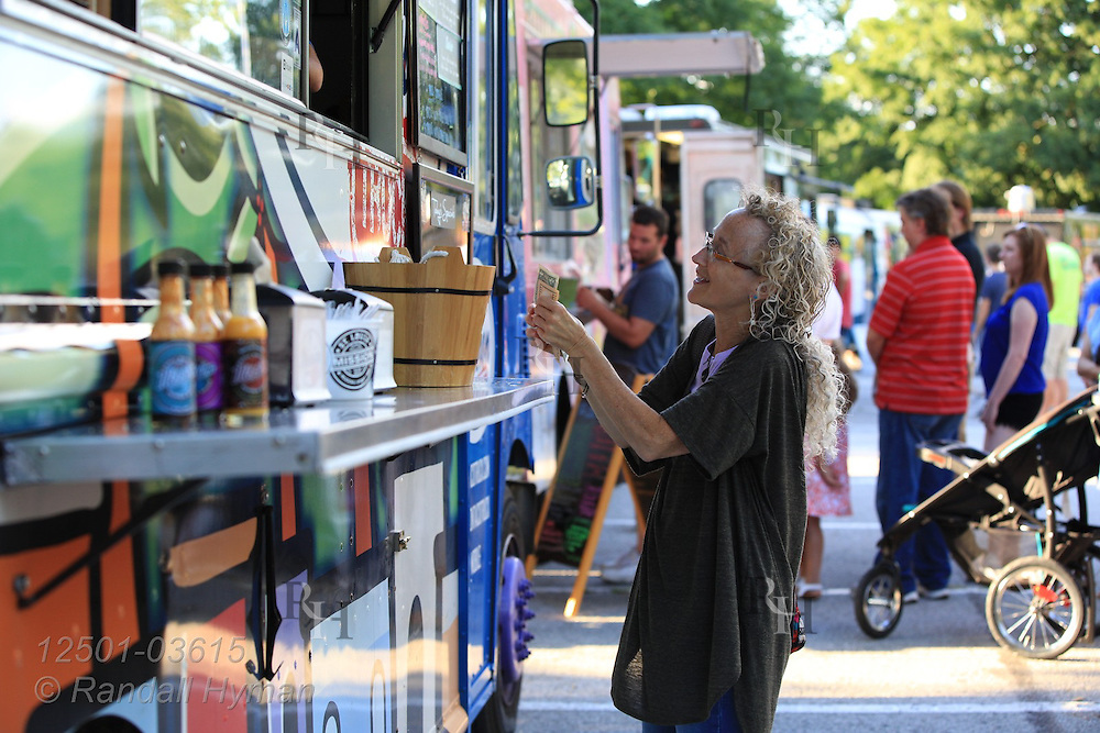 Writer Susan Zimmerman pays for dinner on a summer evening in Jefferson Barracks Park during one of many Food Truck Fest events sponsored by St. Louis County Parks throughout summer; St. Louis, MO