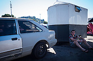 A man leans on a converted horsebox (converted into a caravan) at the site set up for football fans who had nowhere to stay but the tents, campervans, cars and caravans that they had bought with them. The site, at the Terreirao Do Samba, Rio de Janeiro, Brazil, was arranged by the city government once they realised the number of fans in this situation was significant and rather than having them scattered about the sity they offered secure, enclosed accommodation with sanitation and water. The majority of fans at the site were Argentinian but there were also people from Chile, USA, Uruguay and Colombia. Photo by Andrew Tobin/Tobinators Ltd