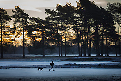 © Licensed to London News Pictures. 18/01/2017. Walton on the Hill, UK. A runner braves the cold as the sun rises on a frosty Walton Heath south of London. Britain is continuing to experience a cold spell. Photo credit: Peter Macdiarmid/LNP