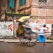 A rickshaw pull runs by communist party signs on the streets of Kolkata. Kolkata, India