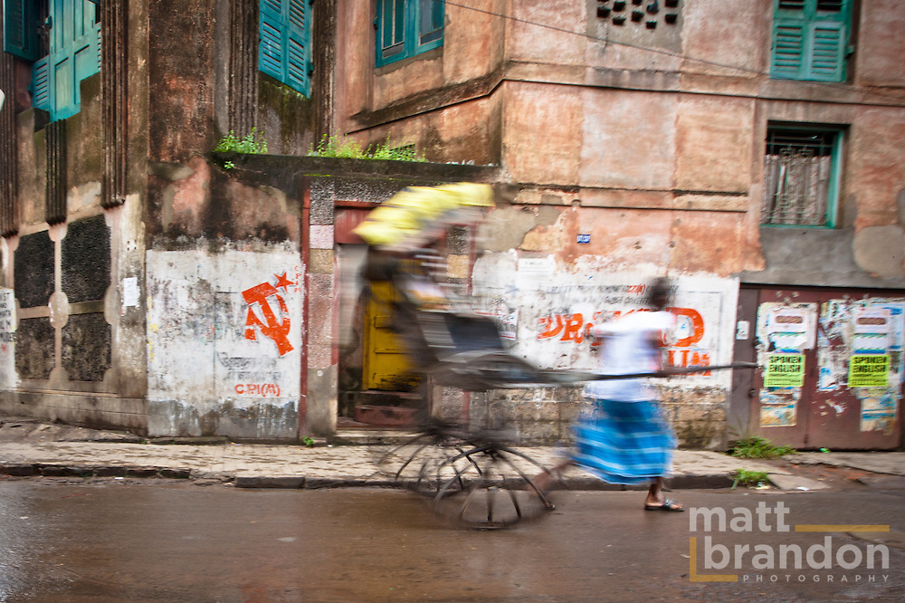 A rickshaw pull runs by communist party signs on the streets of Kolkata. Kolkata, India