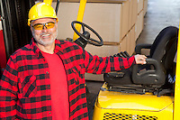 Man standing by fork lift truck smiling