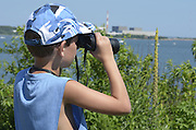 "Niantic, Connecticut, July 6, 2012 - From a high vantage point at McCooks Point Park, seven-year-old Nathanial ""Nate"" Tirrell of Southbury, CT looks out to sea with binoculars as some of the tall ships begin to appear in Niantic Harbor."
