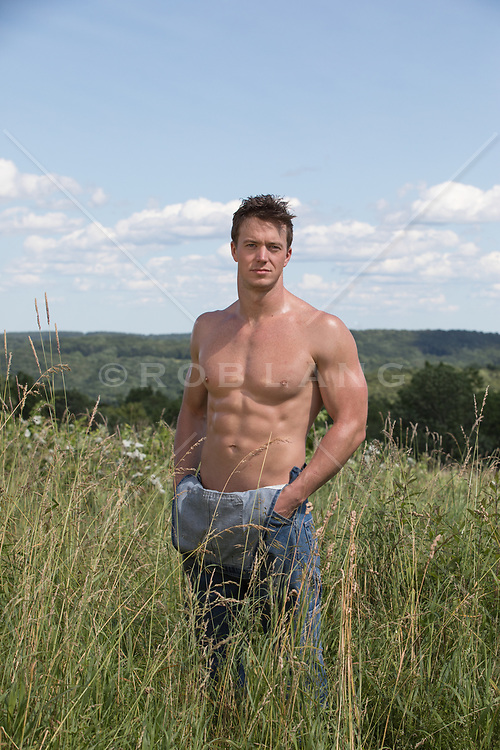 hot guy in overalls and no shirt in a field