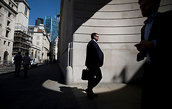 © Licensed to London News Pictures. 25/06/2018. London, UK. City workers pass a circle of sunlight formed at the corner of the Bank of England as high temperatures remain in most of the UK. Photo credit: Peter Macdiarmid/LNP