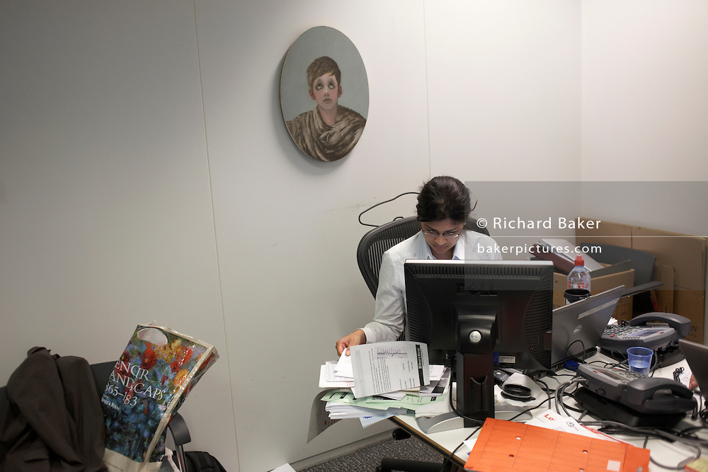 A casually-dressed accountant works in a cluttered office cubicle in an auditing company's London headquarters.