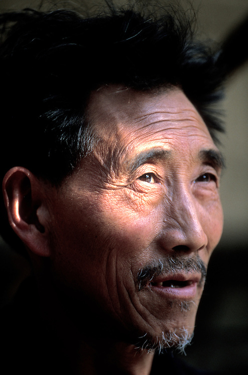 China, Sichuan Province, Fengjie, Portrait of merchant at street market in city along banks of Yangtze River