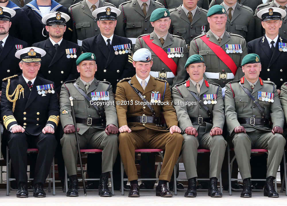 Prince Harry takes part in a group photograph with the Royal Marines Tamar at the HM Naval Base in Devonport, Plymouth, Friday, 2nd August 2013<br /> Picture by Stephen Lock / i-Images