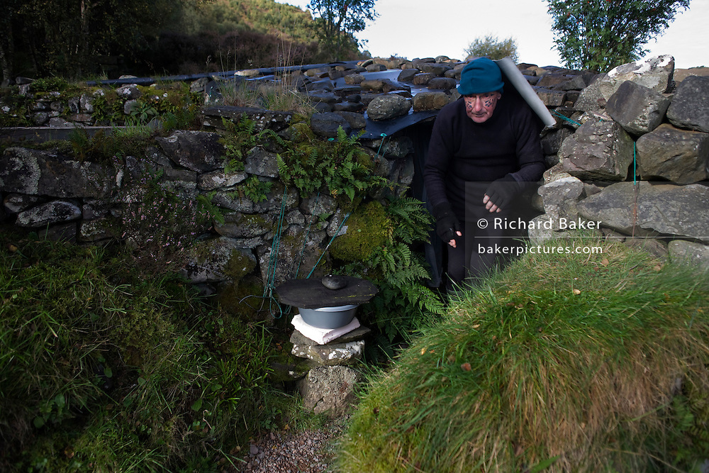 Hermit, Tom Leppard 72, has been living in seclusion at this unidentified spot on the Isle of Skye, Scotland for 22 years. He crouches as he emerges from his self-made shelter, largely cut-off from the outside world. Converting the north-facing dry-stone walls into a home against harsh Scottish winters, he uses a knowledge of survival skills to help him stay fit and largely healthy although his memory is fading and muscular ailments trouble him. Few know his exact whereabouts but concerned locals visit when weather prevents him from crossing a 2km-wide Loch in an old canoe. A tarpaulin roof is weighted down by heavy rocks as winds can be fierce this far north. His days are spent washing, cleaning and carrying out maintenance jobs that keeps his home clean and fresh. Tom is a former solder and sailor and chose this spot when he sought solitude.
