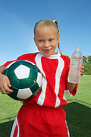 Girl (7-9 years) soccer player holding ball and water bottle, portrait