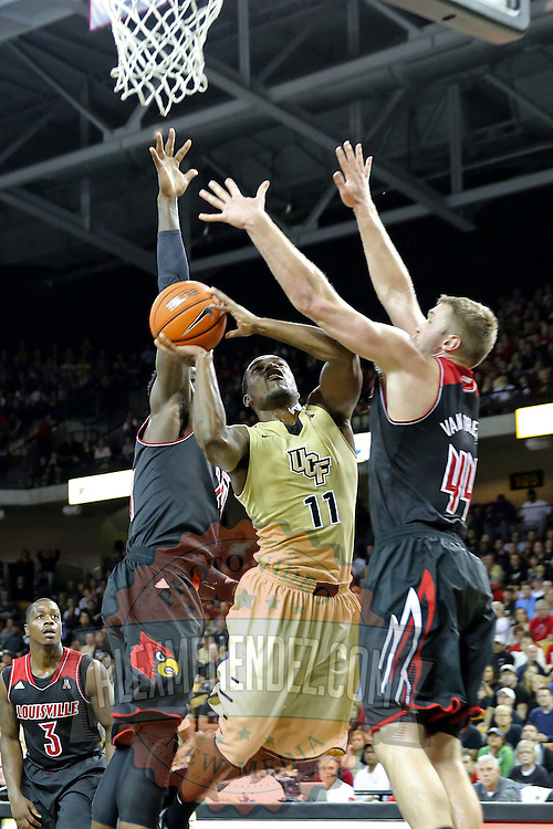 UCF Knights guard Calvin Newell (11) drives the ball to the basket against Louisville Cardinals forward Stephan Van Treese (44) during an NCAA basketball game between the 14th ranked Louisville Cardinals and the UCF Knights at the CFE Arena on Tuesday, December 31, 2013 in Orlando, Florida. (AP Photo/Alex Menendez)
