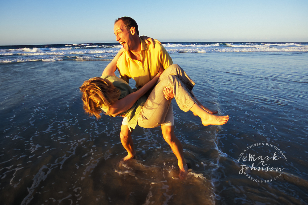Couple playing around on beach, Queensland, N. Stradbroke Island, Australia