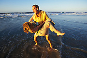 Couple playing around on beach, Queensland, N. Stradbroke Island, Australia people ****Model Release available