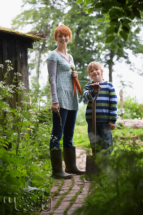 Mother and son (5-6) with spade in countryside portrait