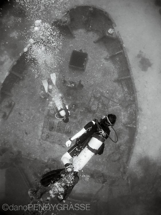 Scuba divers float above the bow of the El Aguila shipwreck in Roatan, Honduras.