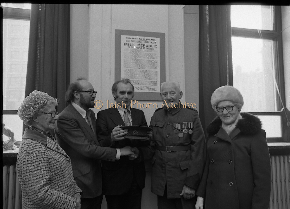 1916 Uniform Is Presented to The National Museum..(L8)..1977..23.04.1977..04.23.1977..23rd April 1977..Today Sean Duffy will parade his Irish Volunteer uniform for the last time as he wears it before he presents it to the National Museum, Kildare Street, Dublin. He wore the uniform on active service in the North Brunswick/North King Street theatre of operations in Easter Week 1916. He also managed to wear the uniform while held in detention in both England and Wales in the aftermath of the rising...Image shows Sean Duffy at the ceremony to present his uniform to the National Gallery. Included are from left, Ms Bridie Duffy (sister of Sean), Padraig O'Snodaigh, Assistant Keeper of the National Museum, Sean O'Teachrain, Keeper , Art and Industry Division, Sean Duffy and his sister Ms Annie Woods. On the wall behind them is a copy of the proclamation read out at the G.P.O.in 1916.