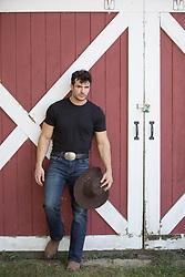 hot cowboy leaning against a barn