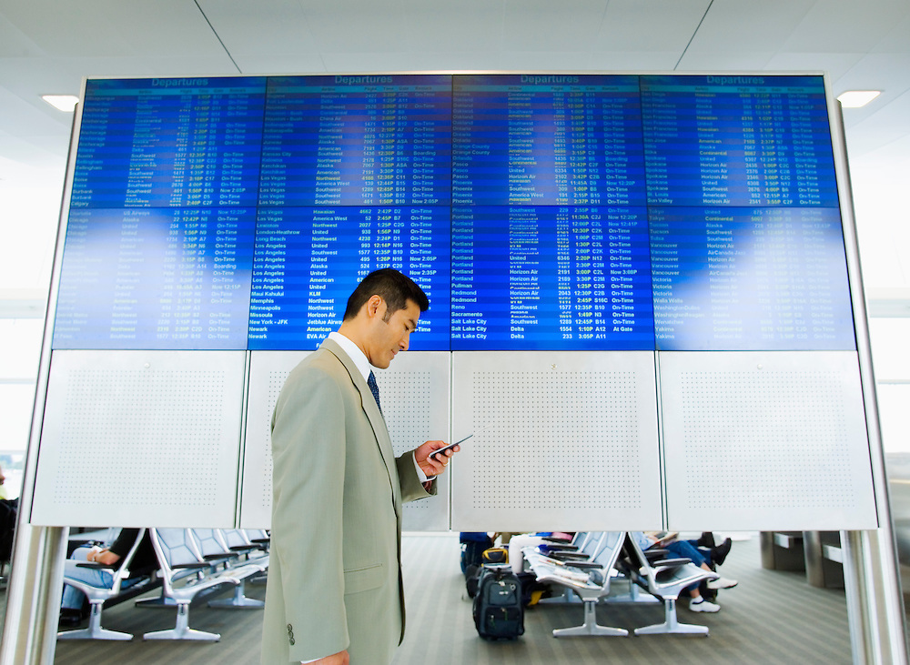 A mid 30's Asian business man standing below an arrivals / departures display in an airport looking at his travel documents.