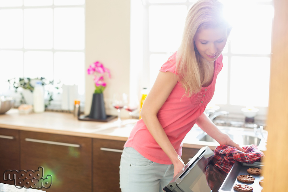 Mid adult woman baking cookies in kitchen