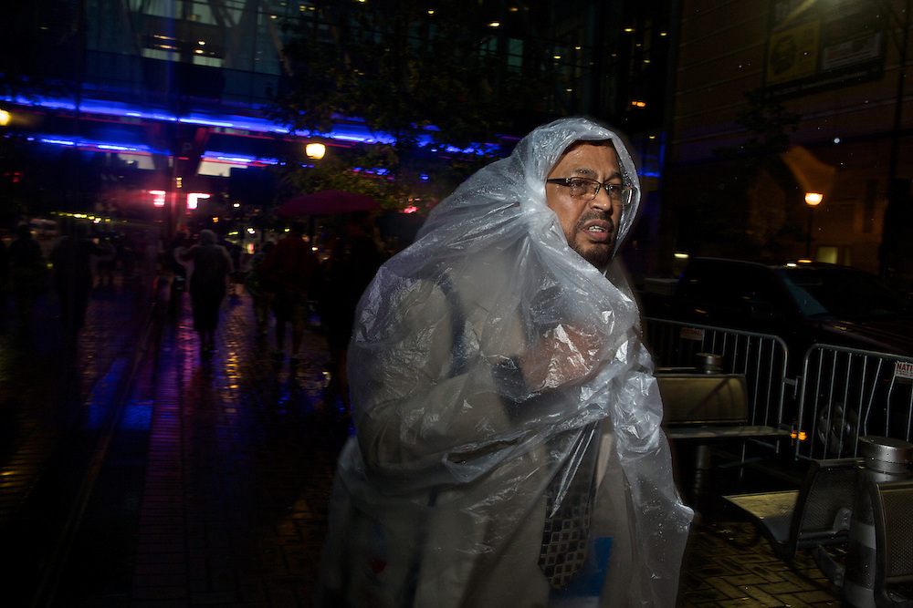 Attendees of the 2012 Democratic National Convention protected themselves from ongoing rain as they walked around downtown Charlotte on Tuesday, September 4, 2012 in Charlotte, NC.