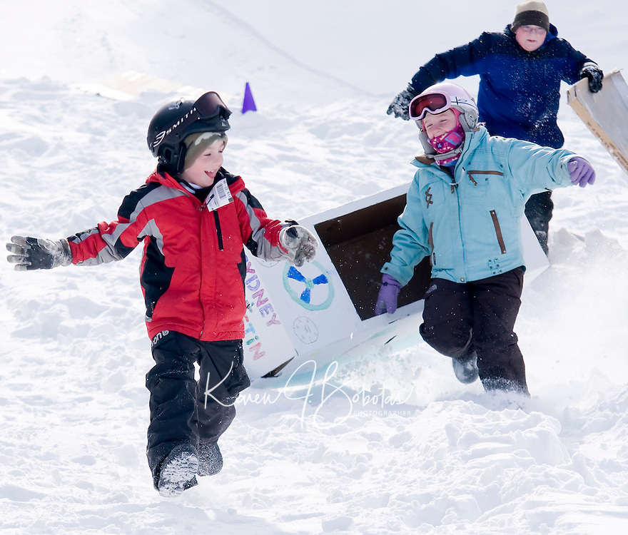 Austin and Sydney's car runs out of gas in the soft snow at Gilford Outing Club so they run it down the slope Wednesday morning during the Cardboard Box Derby held as part of Gilford Parks and Recreation week long winter celebration.  (Karen Bobotas/for the Laconia Daily Sun)