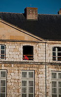 Our Lady of Chartres Cathedral, Chartres, France. Restoration work - man working on an upper window of the house.