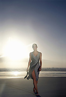 Woman walking on beach against sunset