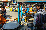 Vendors prepare an order for a customer at a food stall at a street market in Waragal, Telangana, Indiia, on Sunday, February 10, 2019. Photographer: Suzanne Lee for Safe Water Network