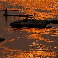 Fisherman in boat on Mekhong river at sunset, Luang Phrabang, Laos