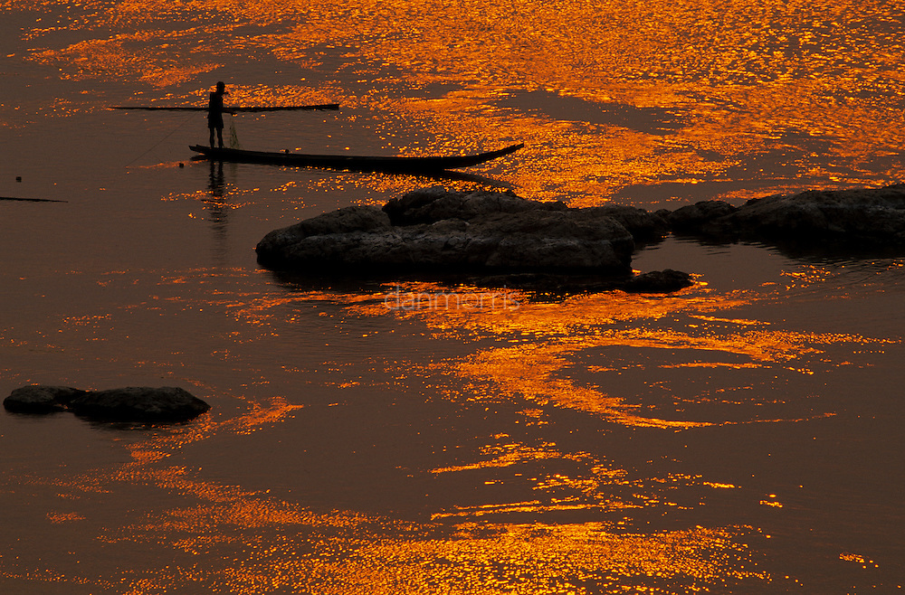 Fisherman in boat on Mekhong river at sunset, Luang Phrabang, Laos