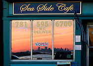 The Boston Skyline reflecting in the window of a restaurant in Swampscott, MA at sunset.