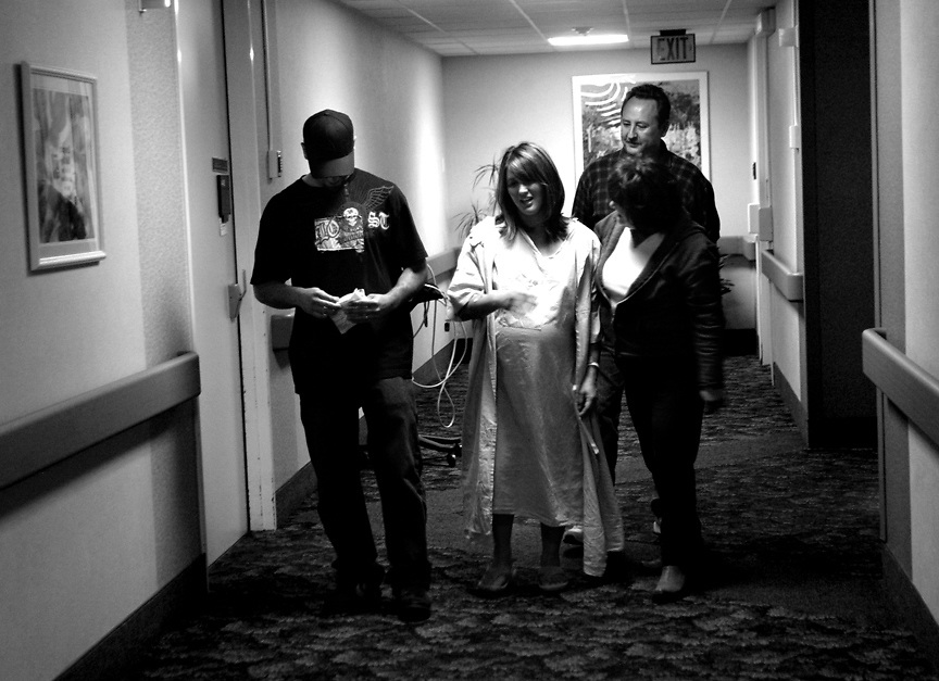 Mike (left) and Melanie Dahlan (center) are joined by Melanie's mom Rachel Long and step-father Mark Long on a walk around the Birthing Center at Palomar Medical Center to ease the pain of contractions. The Dahlans arrived at about 4am with Melanie dialted to between four and five centimeters. Bringing life into the world. A young couple experiences the birth of their first child.