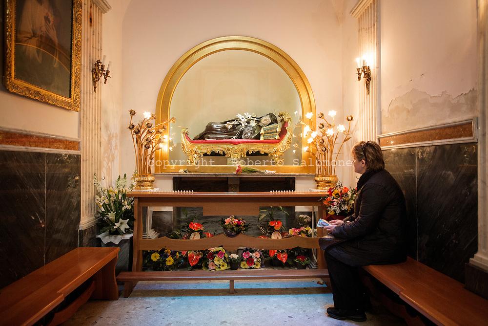 Napoli, Italia - 6 marzo 2014. Fedeli pregano all'interno del convento di Santa Maria Francesca delle cinque piaghe nei quartieri spagnoli di Napoli. All'interno del convento è presente all'interno del convento vi è una sedia ritenuta miracolosa dai fedeli.  Essa è la sedia dove solitamente Maria Francesca sedeva per riposare Questo rituale è particolarmente seguito dalle donne sterili che desiderano il concepimento di un figlio. Oggi chi vuol chiedere una grazia alla santa, vi si siede e le rivolge una preghiera.
