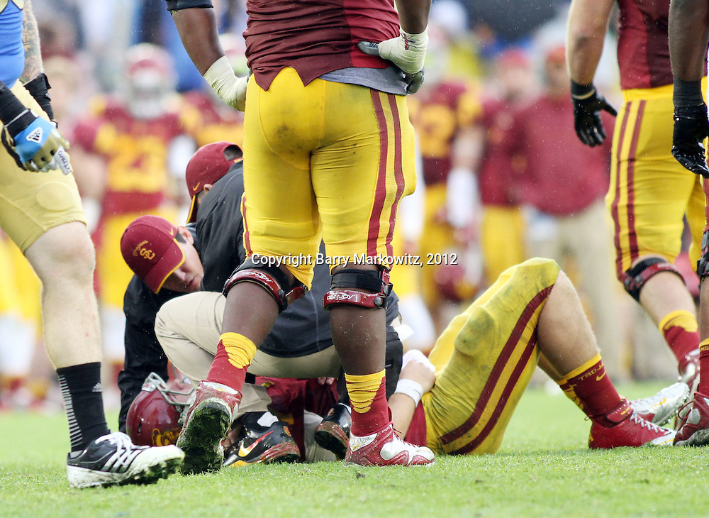 USC QB preseason Heisman favorite, Matt Barkley, lay on the turf 4th Quarter with a suspected shoulder injury after being sacked by UCLA Bruin Outside Linebacker, Anthony Barr.  The UCLA Bruins defeated the USC Trojans 38-28 for the Pac 12 South Championship at the Rose Bowl, Pasadena, California.  Photo by Barry Markowitz, 11/17/12, 12pm