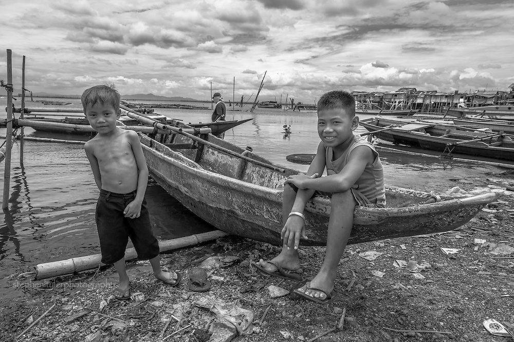 Everyday life in a fishing village community with nearly everything built from bamboo on top of stilts on the edge of a lake. Two boys sitting in a banca