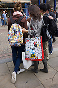 Foreign tourists and a Disney merchandising bag with the image of Minnie Mouse, in Cambridge, England.