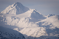 Four Winds Mountain near Haines, Alaska and near the border with Alaska and British Columbia, Canada is bathed in afternoon sunlight. This view of the mountain is from the Alaska Chilkat Bald Eagle Preserve. Mountains in the Haines area are a popular destination for heli-skiing.