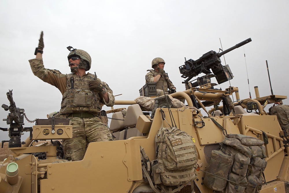Captain Frank Reeves (left) of 16 Air Assault Bde's elite BRF (Brigade Reconnaissance Force) signals to his men as they move from compound to compound searching for weapons and explosives as part of an operation in the Western Dasht, Helmand Province, Southern Afghanistan on the 18th of March 2011.