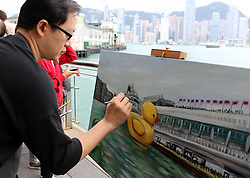 59594169  .A painter draws the scene where a huge rubber duck floating on the waters at the Victoria Harbor in Hong Kong, south China, May 2, 2013. The largest rubber duck was created by Dutch artist Florentijn Hofman, with 18 meters of length, 15 meters of width and height. The duck has visited 12 cities since 2007, May 2, 2013 Photo by: i-Images.UK ONLY