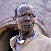 A Dinka man with dry weather beaten wrinkled face, wearing a large blue decorative necklace, SOUTHERN SUDAN, 1997