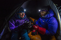 A female mountaineer holds a mug of warm tea on a cold winter night in Mont Blanc Massif.