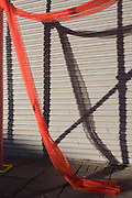 red netting draped across street construction with patterns formed by their shadows.