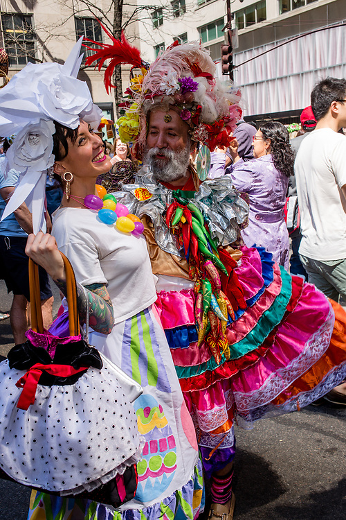 New York, NY - April 16, 2017. New York fixture Oswaldo Gomez in elaborate costume and hat with a parade-goer at New York's annual Easter Bonnet Parade and Festival on Fifth Avenue.