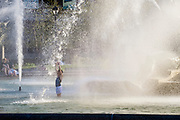 Girl playing in Swann Fountain in Logan's Circle, Philadelphia, Pennsylvania, USA