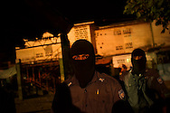 Guards walk through Izalco men's prison at night. Guards are required to wear black ski masks in order to remain anonymous for security purposes.