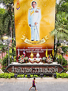 24 JULY 2013 - BANGKOK, THAILAND:    A teenager walks past a large portrait of Bhumibol Adulyadej, the King of Thailand, in front of the headquarters complex of the Royal Thai Police. The King is a revered figure in Thailand and his portrait hangs in front of most government buildings.     PHOTO BY JACK KURTZ